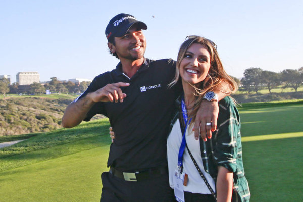 Jason Day, from Australia, waves to fans as he walks off the 16th green of the South course at Torrey Pines with his wife, Ellie, following his playoff victory in the Farmers Insurance Open golf tournament Sunday, Feb. 8, 2015, in San Diego.  Day beat J.B. Holmes on the second extra hole with a par. (AP Photo/Lenny Ignelzi)